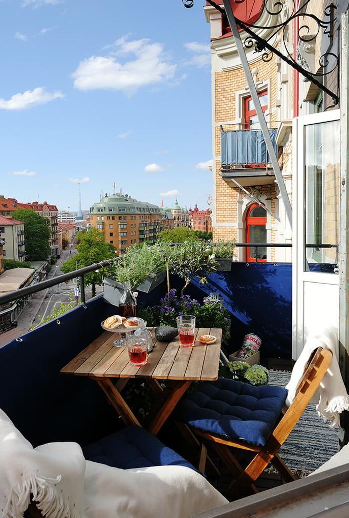 Terrasse mit Aussicht zur Straße, blaue Wand und Kissen, Balkon Lounge klein, kleiner dekorativer Baum