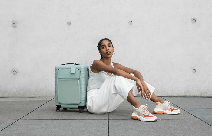 Frau im monochromen weißen Outfit und weiß orange Sneakers, kleiner blauer Handgepäck, Reisegepäck wählen