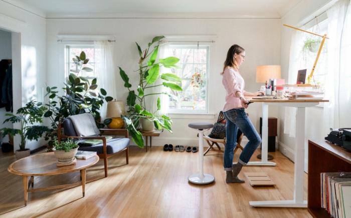 eine junge frau und büro zu hause, tisch und stuhl aus holz, zummer mit vielen pflanzen, home office