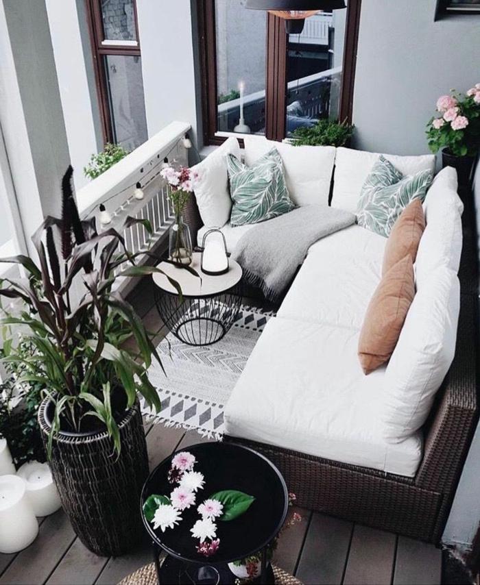 Möbel für kleinen Balkon, Ecksofa mit weißen Kissen, grüne Pflanzen als Dekoration, moderner Korbtisch