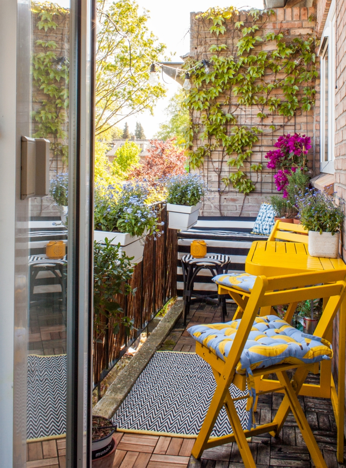Farbige Einrichtung von Terrasse, gelber Tisch und gelbe Stühle, Kletterpflanzen und lila Blumen, Möbel für kleinen Balkon