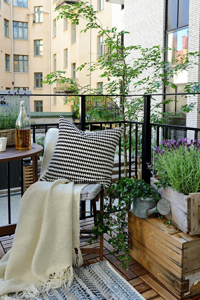 Ikea Outdoor Einrichtung vom Balkon, kleiner Gartenstuhl, schwarz weißer Kissen, Teppich in blauen Tönen, alte Kisten als Dekoration