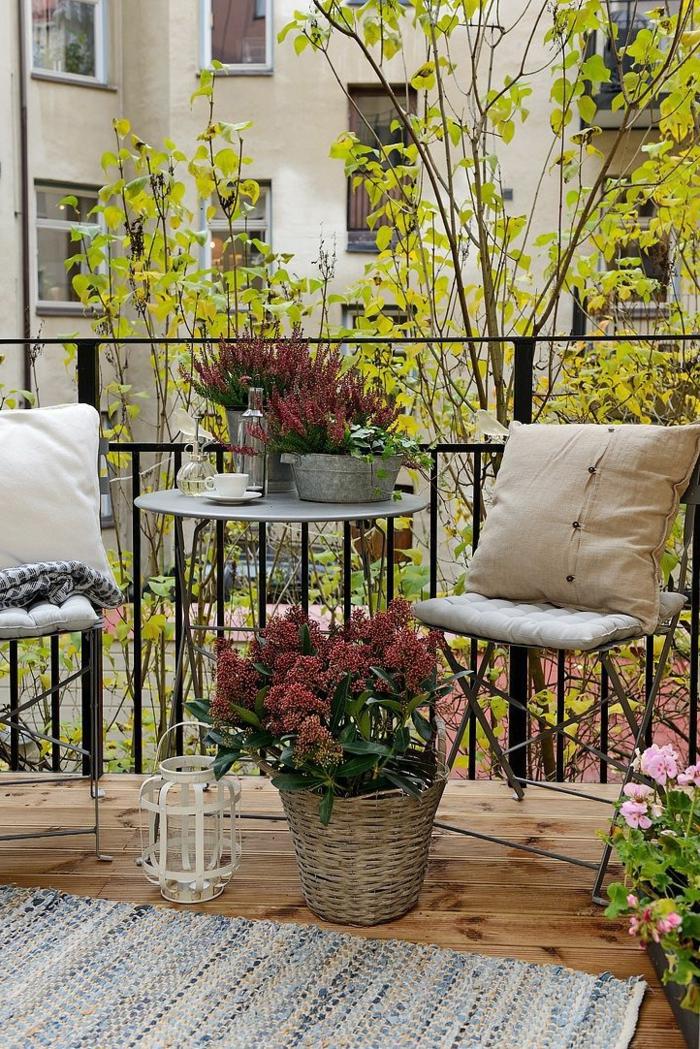 Balkon Inspiration, zwei Gartenstühle mit beigen Kissen, kleine Kaffeetasse auf einem runden Tisch,