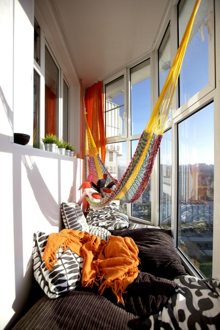 Hängematte auf einer geschlossenen Terrasse, viele große und kleine Kissen, Deko für Garten und Terrasse