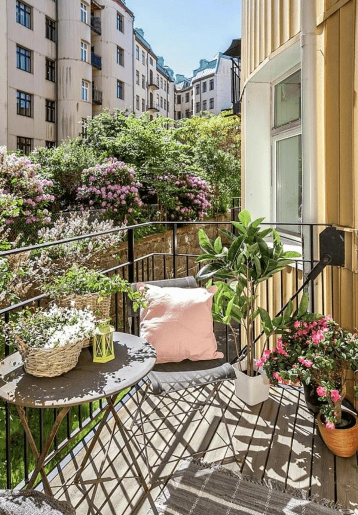Dekoration mit vielen Blumen und Pflanzen, Möbel für kleinen Balkon, pinker Kissen auf grauem Stuhl
