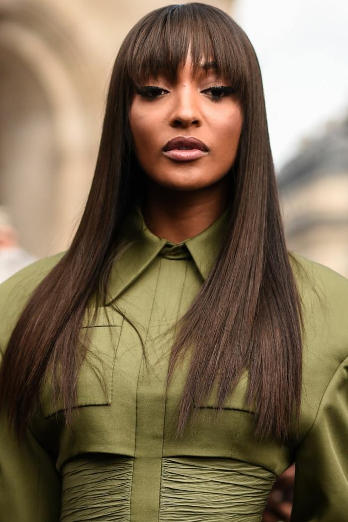 Model Jourdan Dunn, dunkle glatte Haare, Frisuren mit Pony 2020, grünes elegantes Kleid von Balmain, pony styles