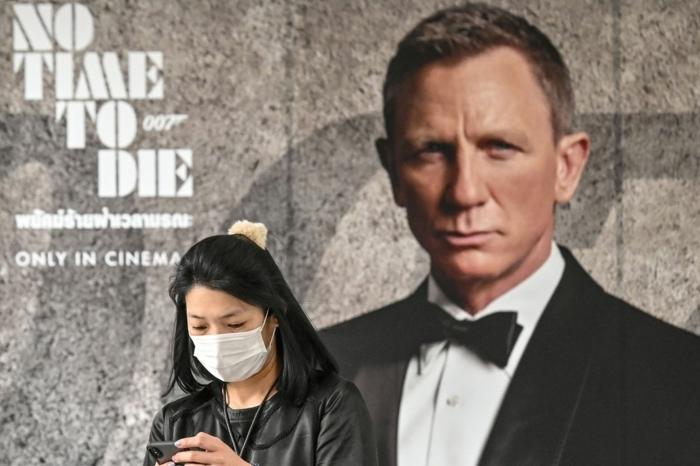 eine frau mit maske gegen coronavirus, poster zu dem film no time to die mit dem schauspieler daniel craig, james bond film