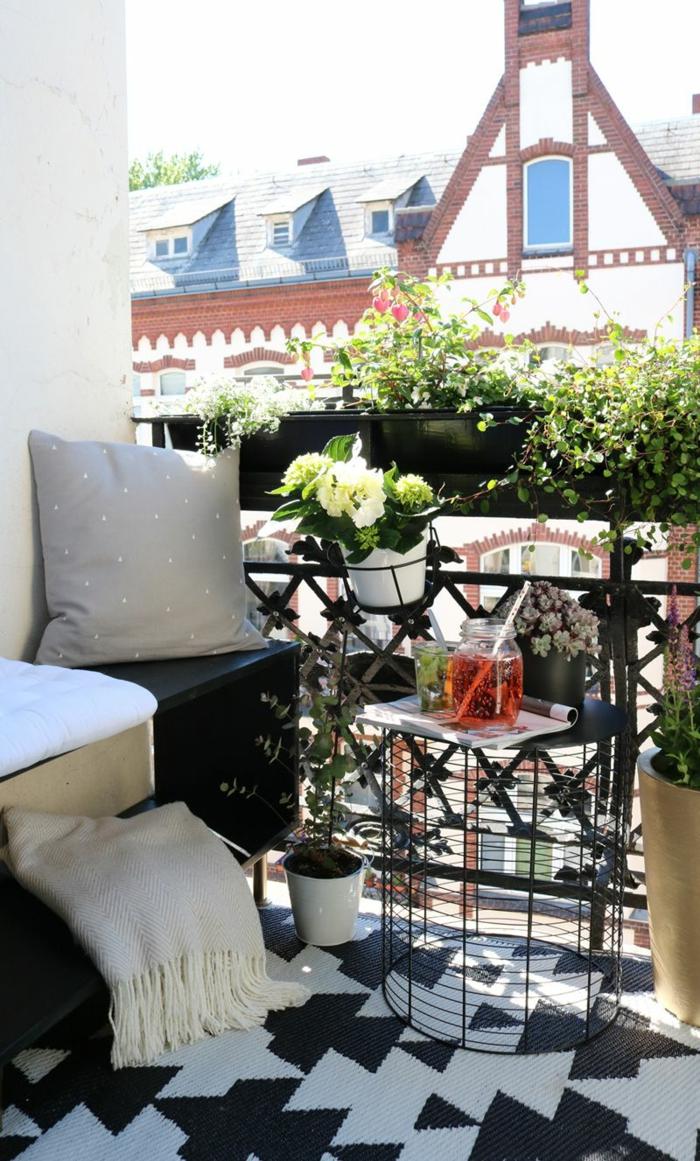 Wunderschöne weiße Blume in einem Topf, geometrischer Teppich in schwarze und weiße Farben, moderner Korbtisch. Balkon Lounge klein