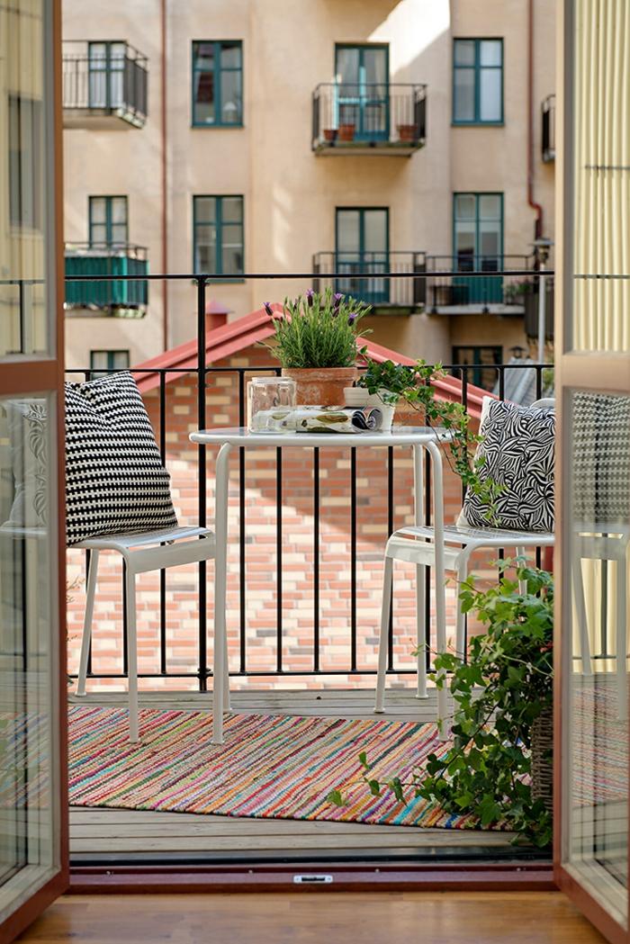 Schlichte Einrichtung einer Terrasse, schwarz weiße Kissen, bunter Teppich, Möbel für kleinen Balkon,