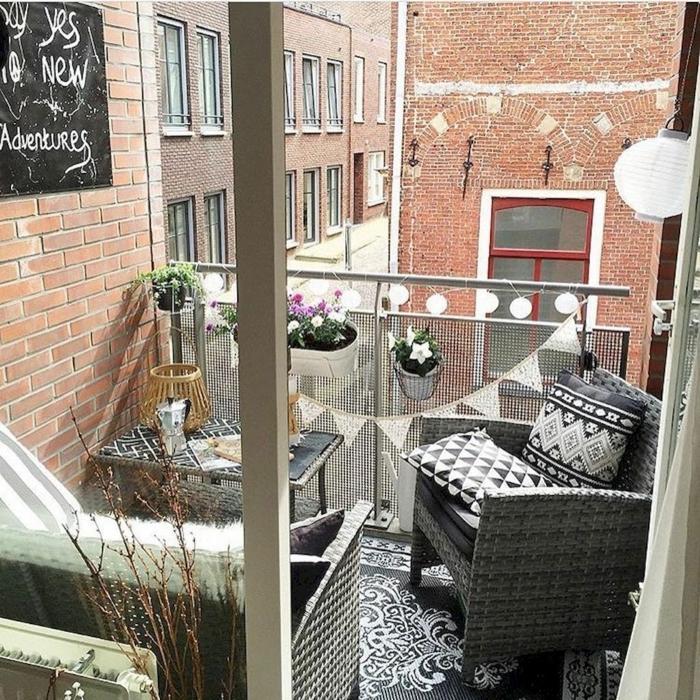 Deko für Garten und Terrasse, zwei graue Sessel, aufgehängte kleine Lampen, Blumen und Pflanzen