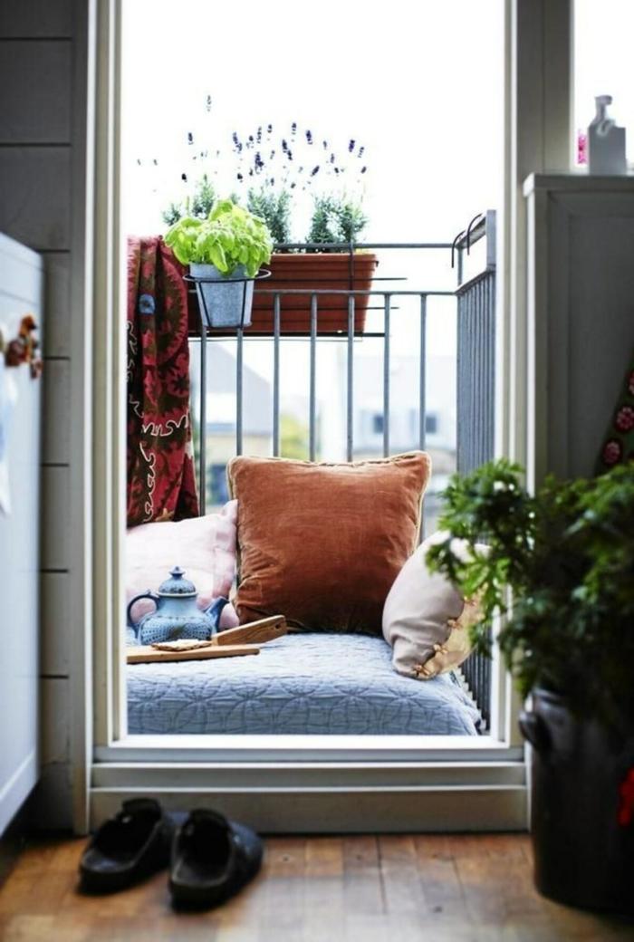 Ikea Balkon gemütlich gestalten mit große Kissen zum liegen, Töpfe mit Pflanzen, Pantoffeln vor der Balkontür,