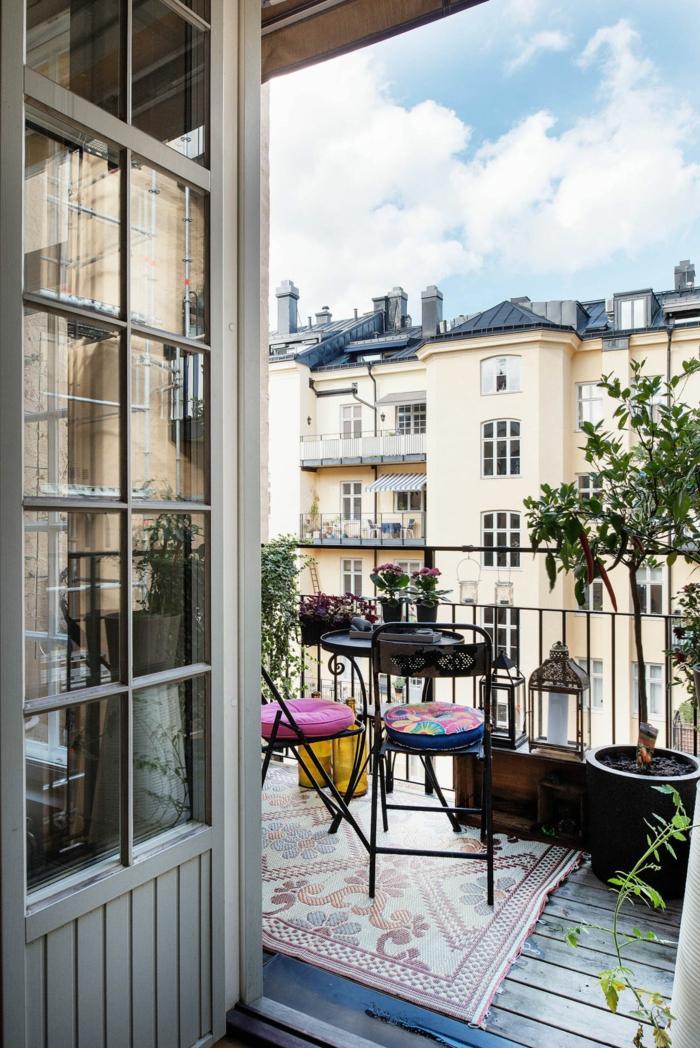 Balkon Inspiration Einrichtung, geometrischer Teppich auf der Terrasse, runder Tisch und Stühle,