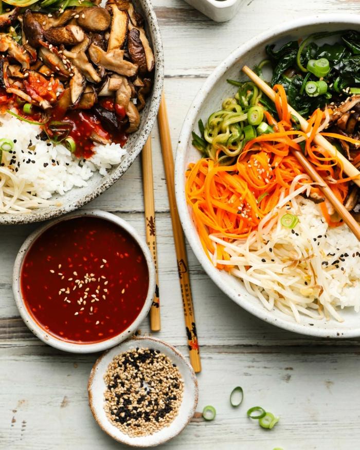 Bibimbap nach koreanischer Art, zwei Bowl mit Reis und Gemüse, Möhren und Pilze, Soße an der Seite, schnelle vegane Rezepte