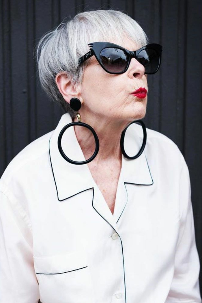 chic gestylete Dame, weißes Hemd, große runde Ohrringe, schwarze katzenaugen Sonnenbrillen, kurzhaarfrisuren mit pony