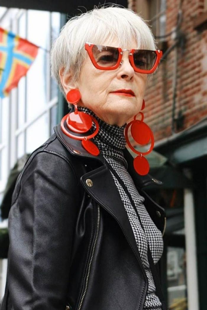 styisch gekleidete älter Dame, schwarze Lederjacke, große rote Ohrringe und Sonnenbrillen, gestufter bob für ältere frauen