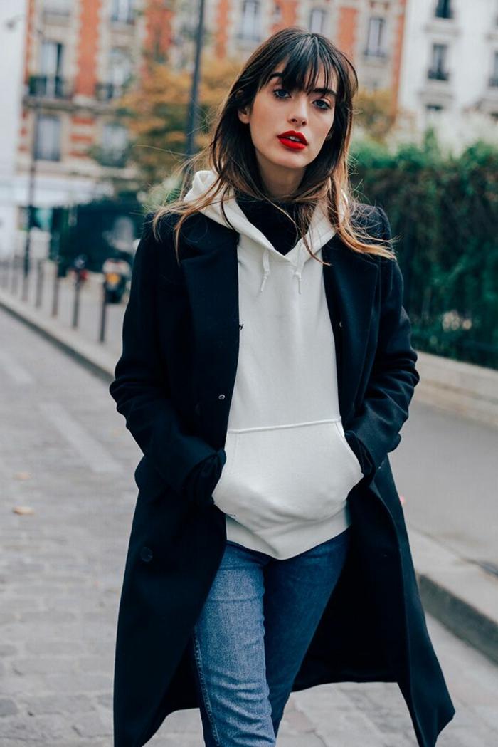 Frau angezogen in Jeans, mit weißem Hoodie und schwarzem Mantel, Street Style Paris, pony selber schneiden,
