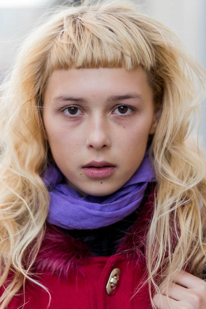 lockige lange blonde Haare, schulterlange haare mit Pony, gekleidet im roten Mantel und lila Schal, Nahaufnahme des Gesichts einer Frau