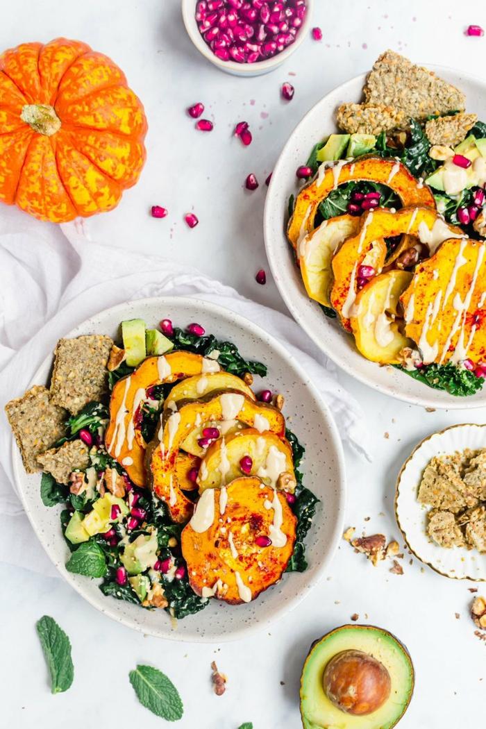 Vegan kochen, zwei Salate mit Grünkohl und gebratener Kürbis, mit Avocado und Granatapfel, garniert mit Kracker,