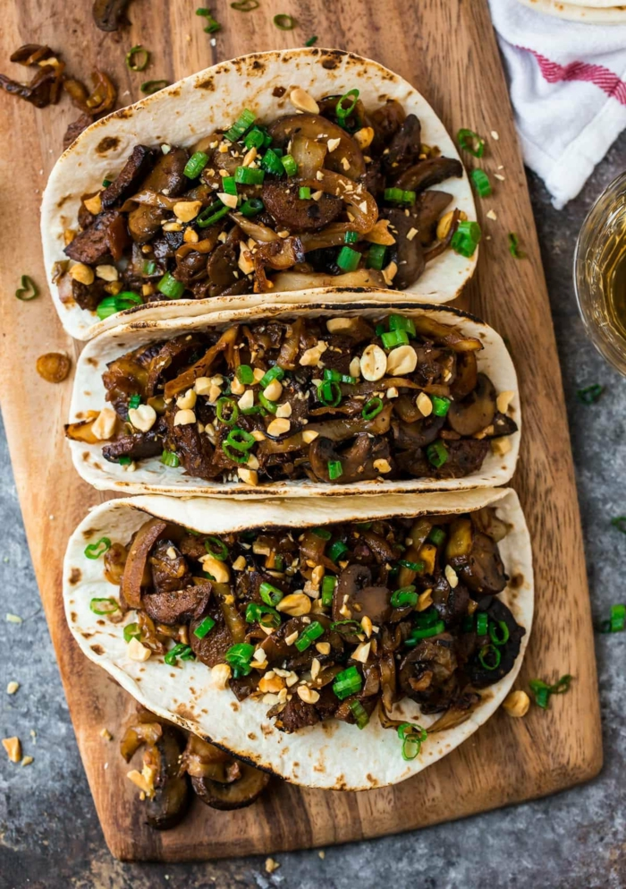 drei leckere vegane Taccos auf einem hölzernen Brett, belegt mit Champignons und Tofu und Erdnüssen, vegan kochen
