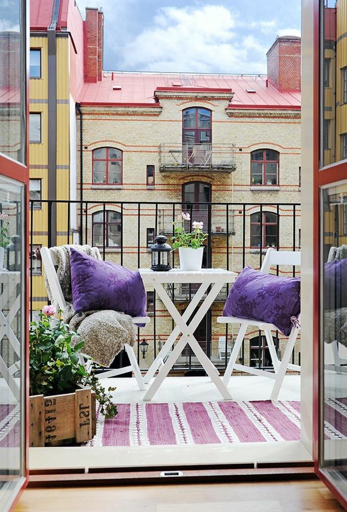 Terrasse Design in lila farbene Kissen und Teppich, Balkonmöbel Set für kleinen Balkon, alter Kiste mit Pflanze