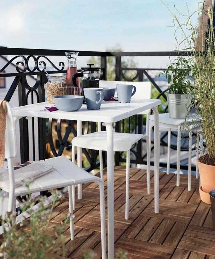 schlichte Einrichtung von Terrasse, weiße Möbel für kleinen Balkon, blaue Tassen und Schalen zum Frühstück