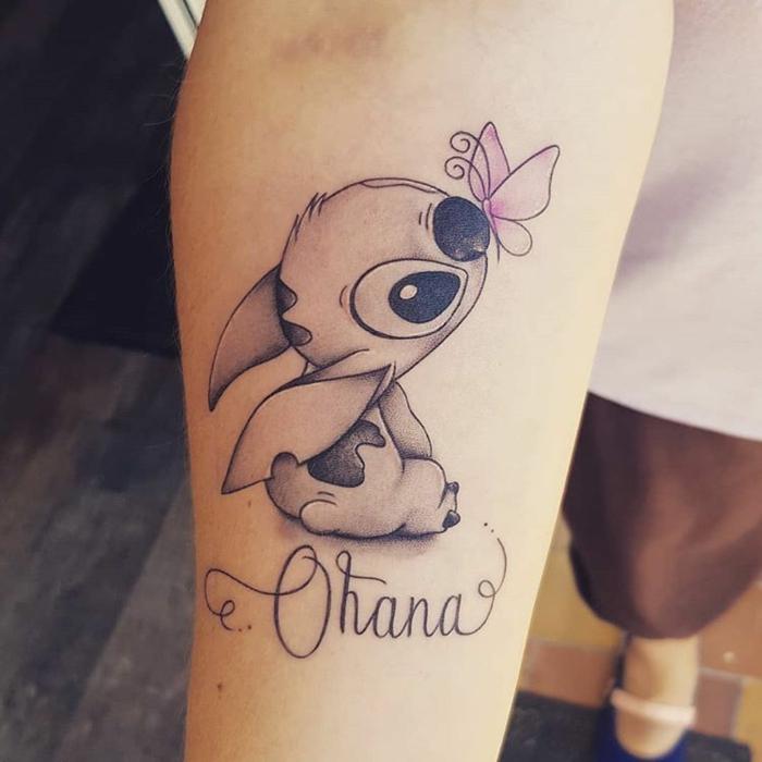 ohana beduetung, zeichen für familie, rosa schmetterling, süße tätowierung am arm, stitch