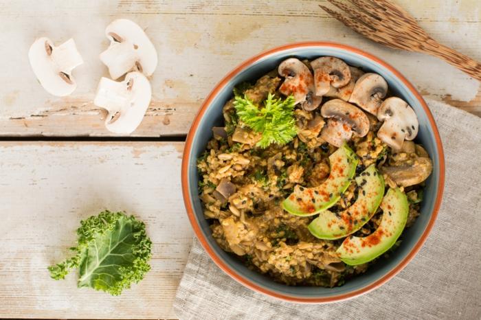 Currybrei nach indischer Art mit Reis Pilzen und Avocados, vegane Hauptgerichte für Gäste, kleine hölzerne Gabel