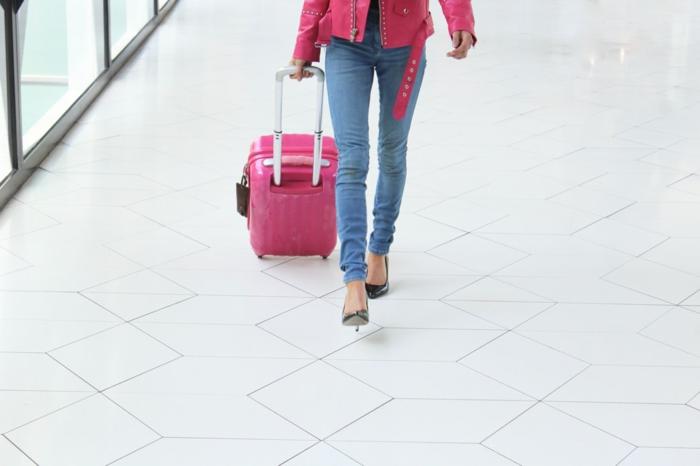 Frau in Jean und pinke Lederjacke mit High Heel, kleiner Handgepäck Koffer, Reisegepäck wählen
