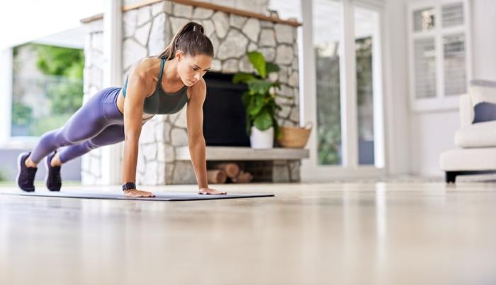 Frau in Plank Position, angezogen in lila Leggings und grünen Sport BH, großes Wohnzimmer, Home Workout