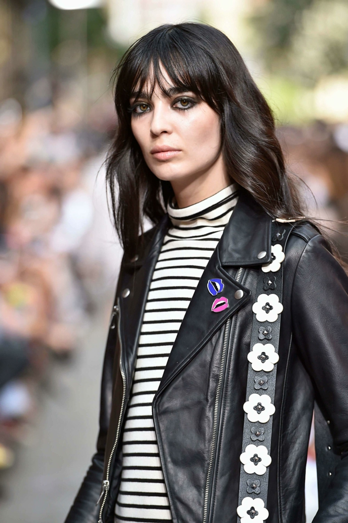 Street Style Fotografie, Fashion Week Mode, Dame in schwarze Lederjacke, schwarz weiß gestreifte Bluse, schwarze Haare, mittellange Haare mit pony