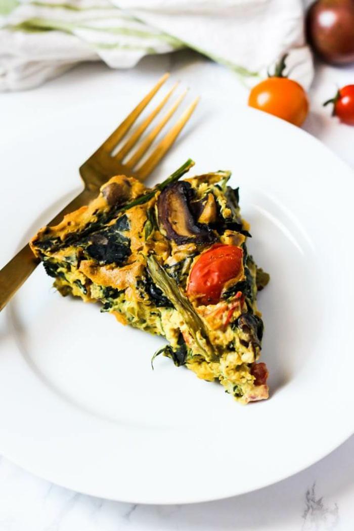 Lecker Gericht des Tages, veganer Quiche mit Tomaten und Spargel auf einem weißen Teller und mit einer Gabel daneben