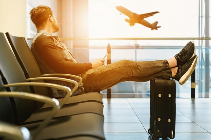 lässig angezogener Mann wartet auf einem Flughafen, kleiner handgepäck koffer, fliegender Flugzeug, das perfekte reisegepäck
