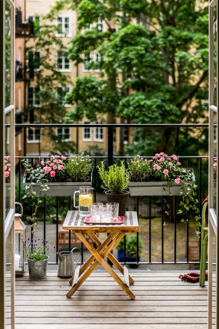 Balkon Lounge Klein, kleiner Esstisch aus Holz, Blumentöpfe mit pinken Blumen, Terrasse Inspiration