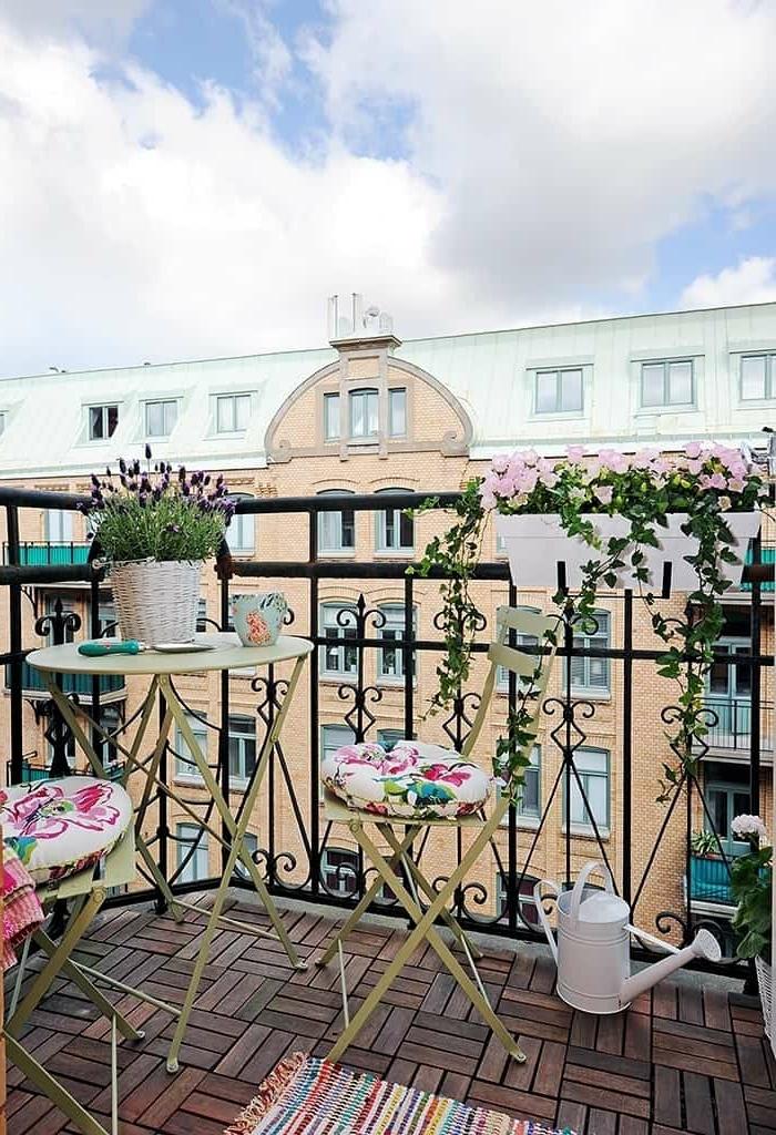 Balkon Lounge Klein, Design mit Blumen und Kissen mit Blumenmotiven, bunter Teppich, weiße Gießkanne
