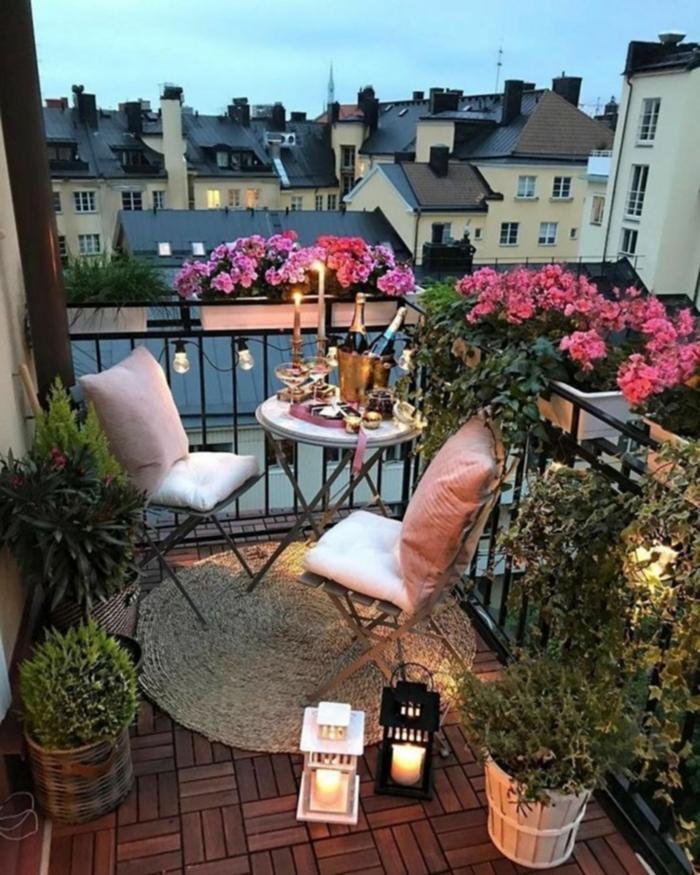 schöne pinke Blumen, Möbel für kleinen Balkon, Kerzen und Champagner, zwei Laternen,