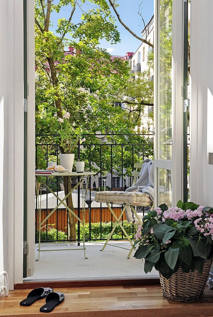 schlichtes Design für Terrasse, Ikea Balkon, Pflanze mit pinken Blüten in einem Korb, weißer Stuhl und Tisch
