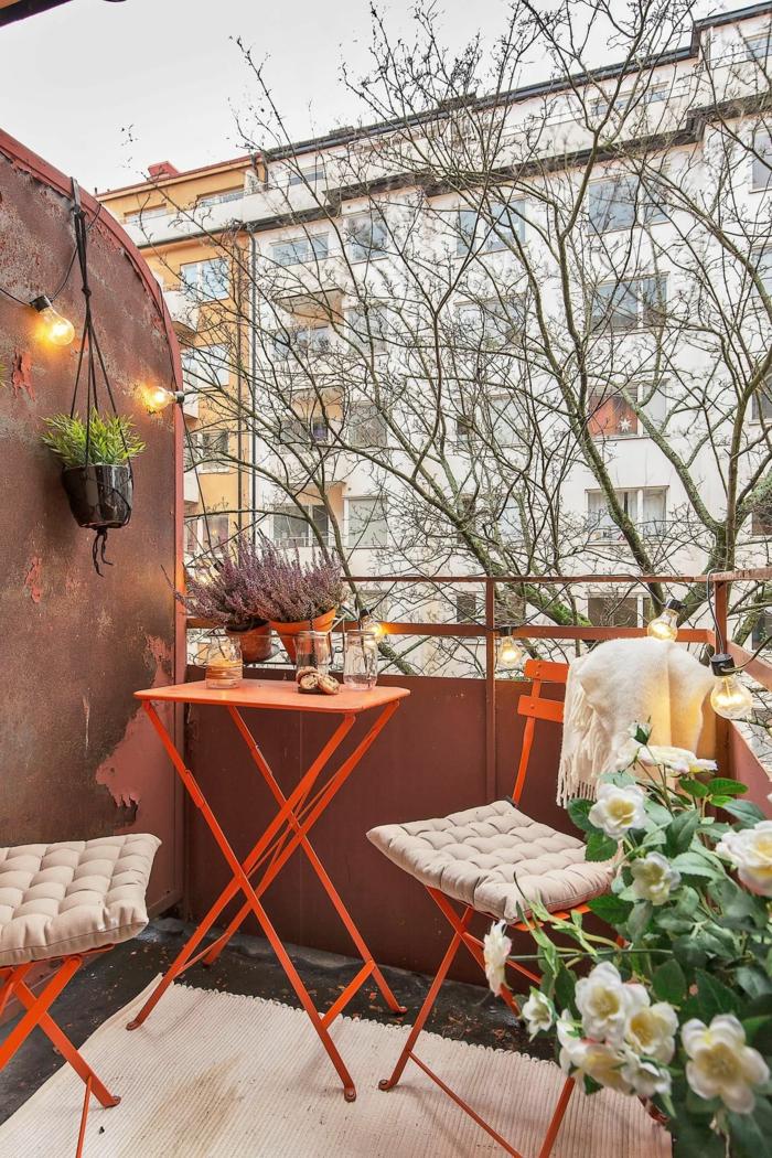 Ikea Outdoor, Balkonmöbel in orange Farbe, schöne Blume mit weißen Blüten, kleine Glühbirnen,