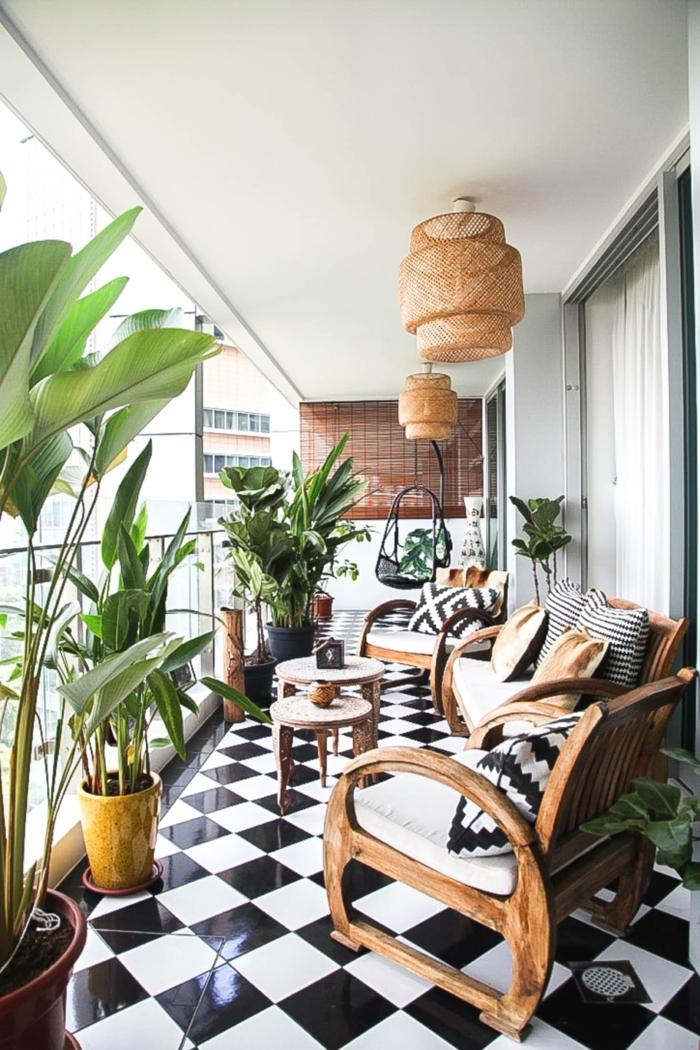 Einrichtung von Terrasse mit modernen Möbel aus Holz, schwarz weißer Boden, viele grüne Pflanzen