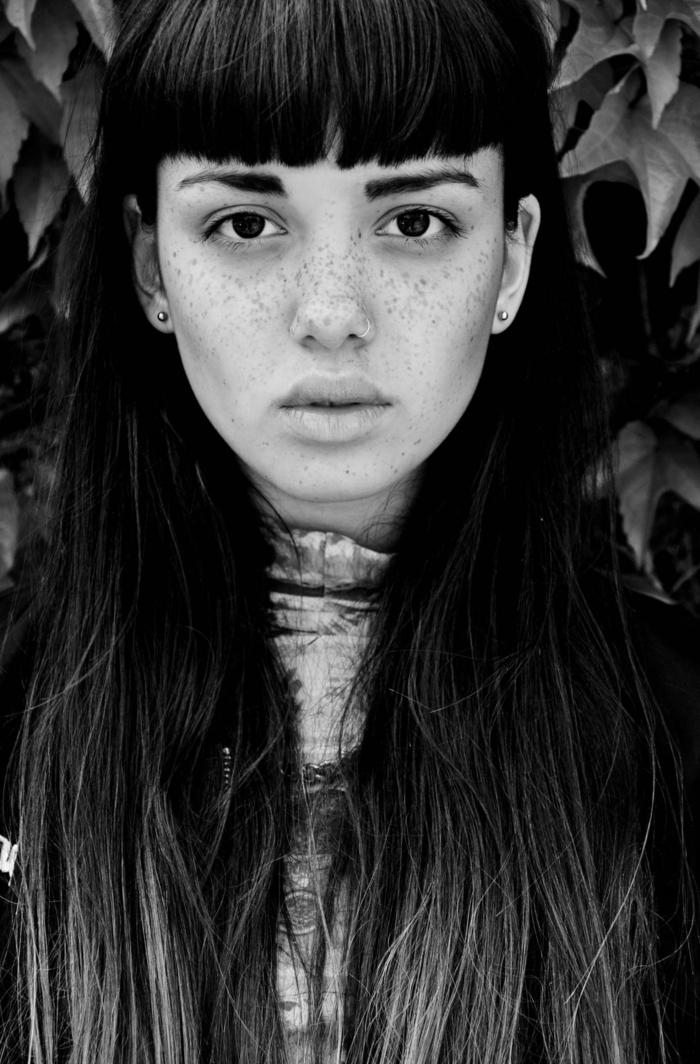 schwarz weiße Fotografie, Frau mit Sommersprossen, schwarze lange Haare mit Pony, kleine perlenohrringe