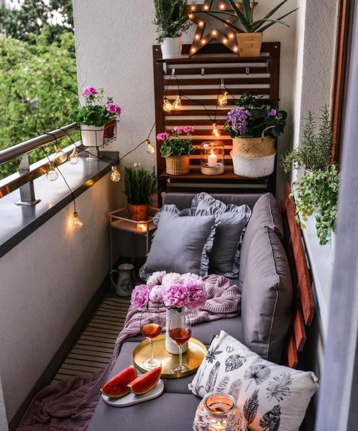 Balkonmöbel set für kleinen Balkon, Sofa mit grauen Kissen, Tablett mit Wein und Wassermelone, Pflanzen und Blumen