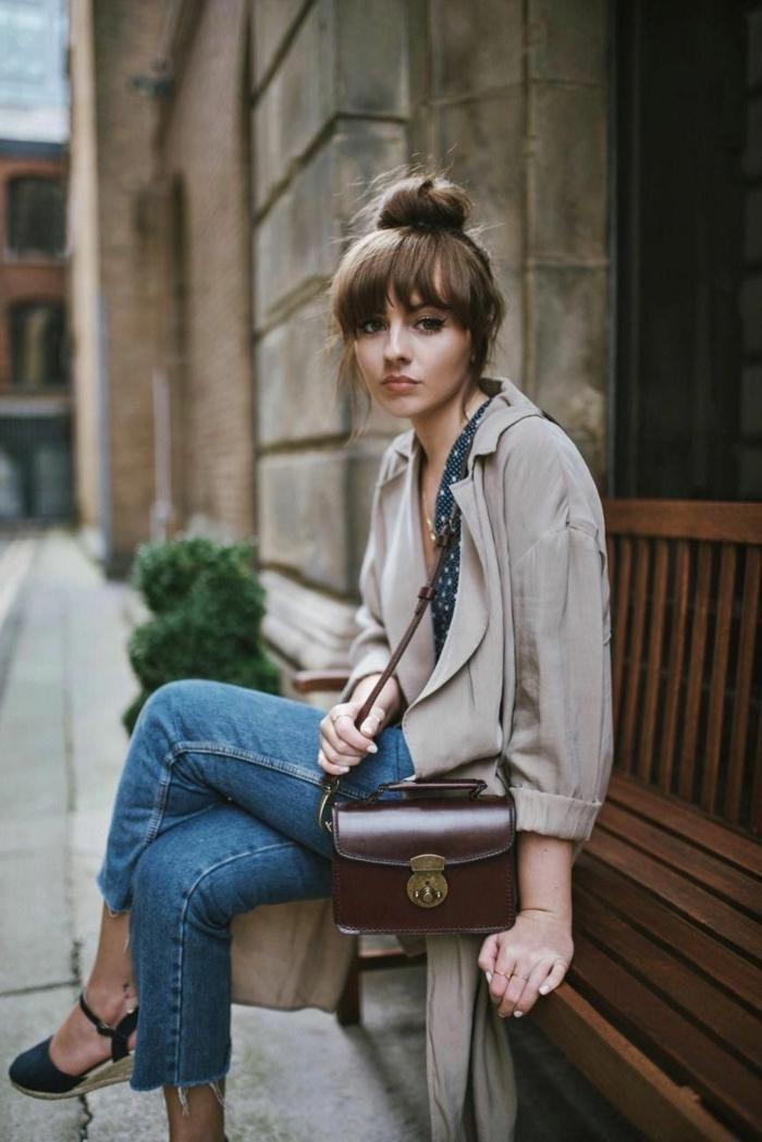 chiche gekleidete Dame sitzt auf einer Bank, gekleidet in einem Trenchcoat und Jeans, kleine Ledertasche, wie sehe ich mit Pony aus, hochgesteckte Frisur im Dutt