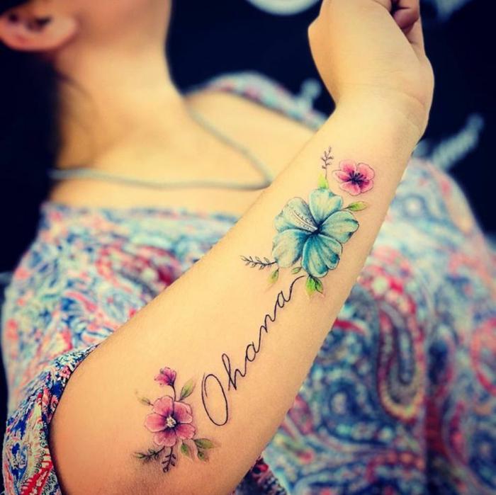 tattoo ideen familie, frau mit wasserfarben tätowierung am unterarm, farbige blüten