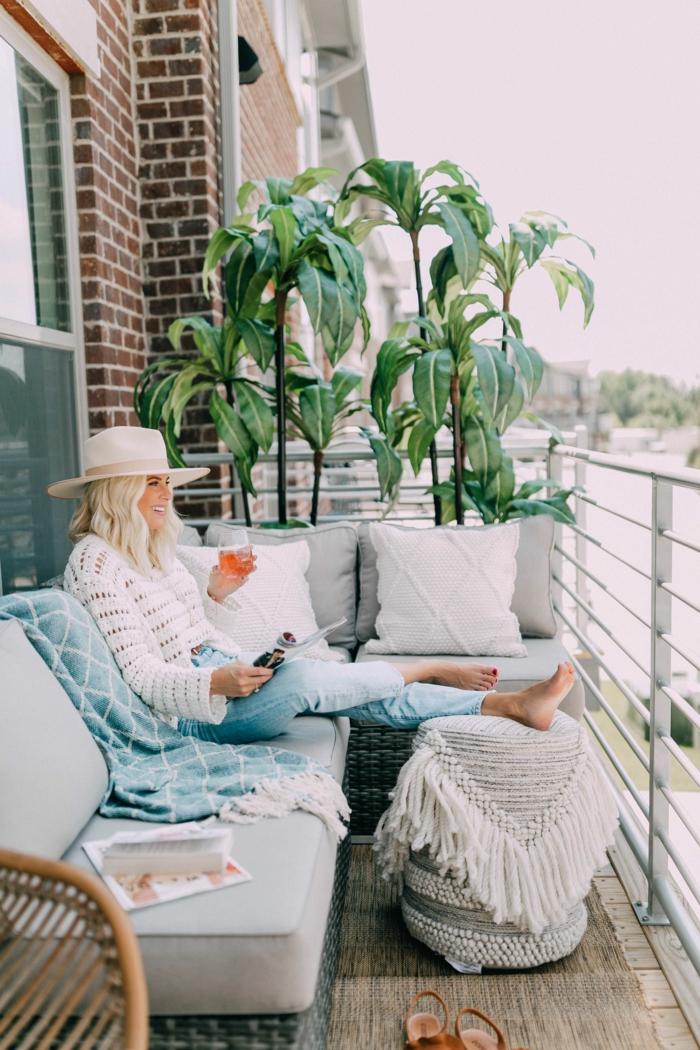 Frau sitzt auf einem Balkon und trinkt Cocktail, angezogen in Jeans und weißem Pullover, Ecksofa in grau, Möbel für kleinen Balkon
