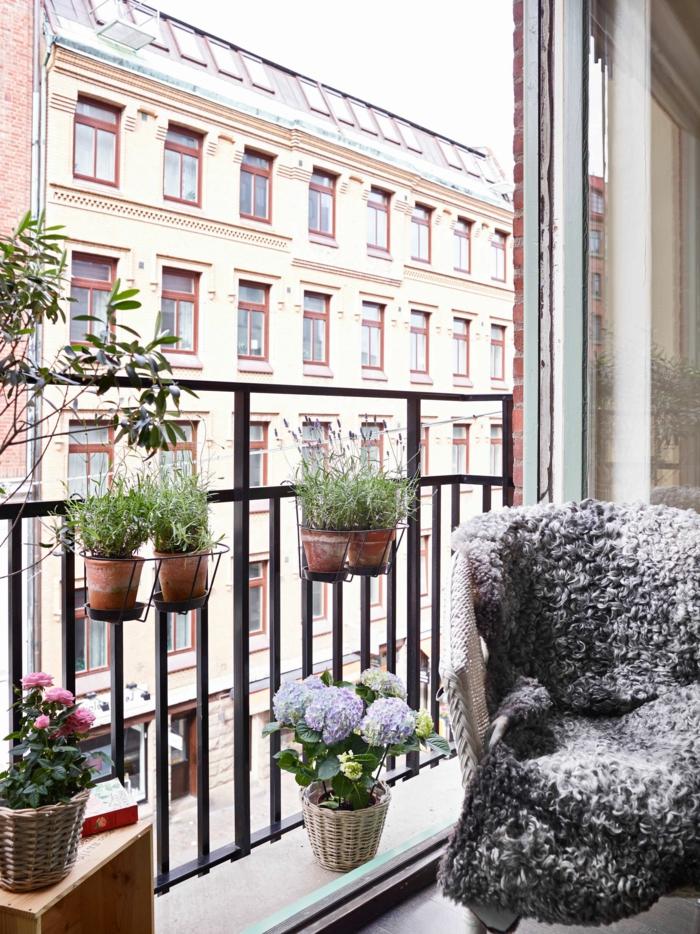 Balkon gestalten Ideen, Sessel mit kuscheliger grauer Decke, kleine Töpfe mit Pflanzen,