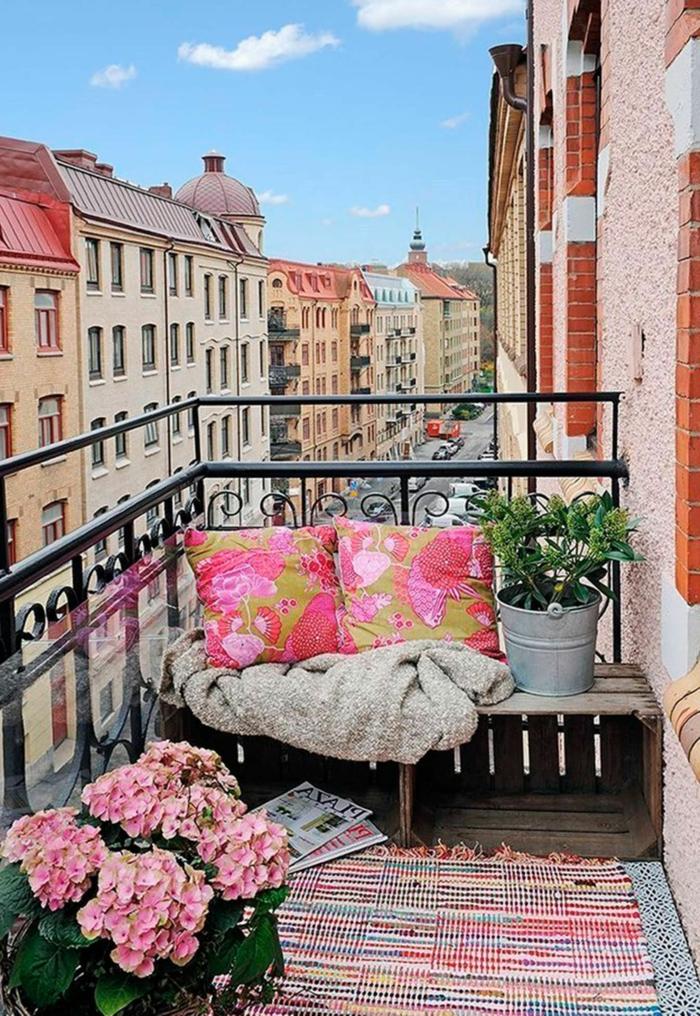 Möbel für kleinen Balkon, Sitzbereich aus alten Kisten, zwei pinke Kissen und bunter Teppich, Blume mit rosa Blüten
