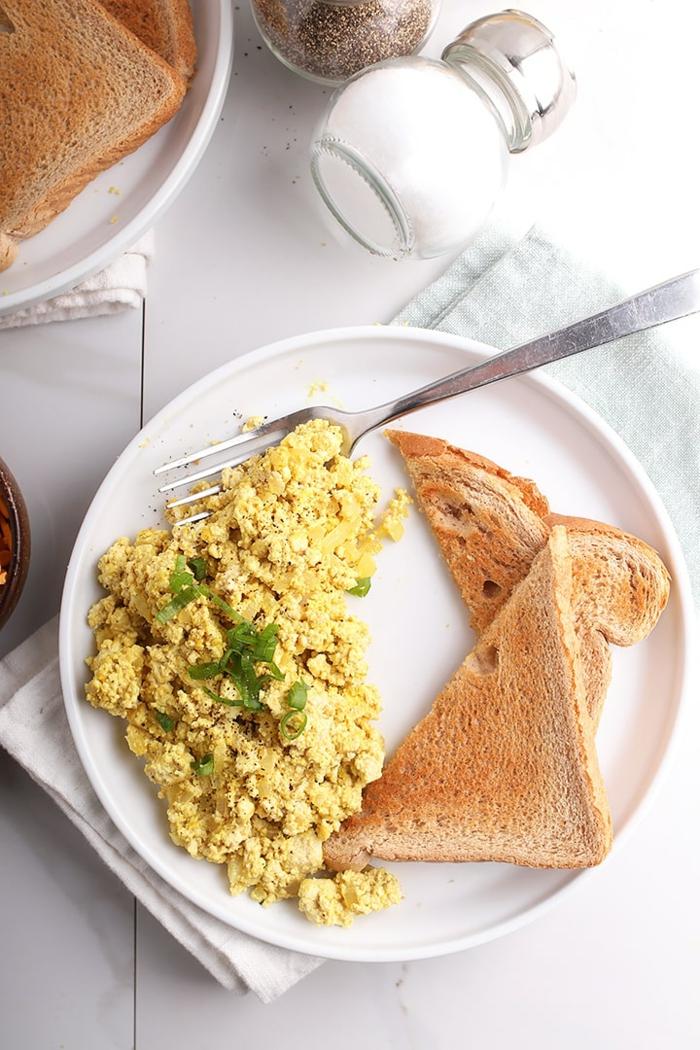 Vegane Rühreier aus Tofu mit zwei Stücken Brot auf einem großen Teller. einfache schnelle Rezepte, großer Salzstreuer