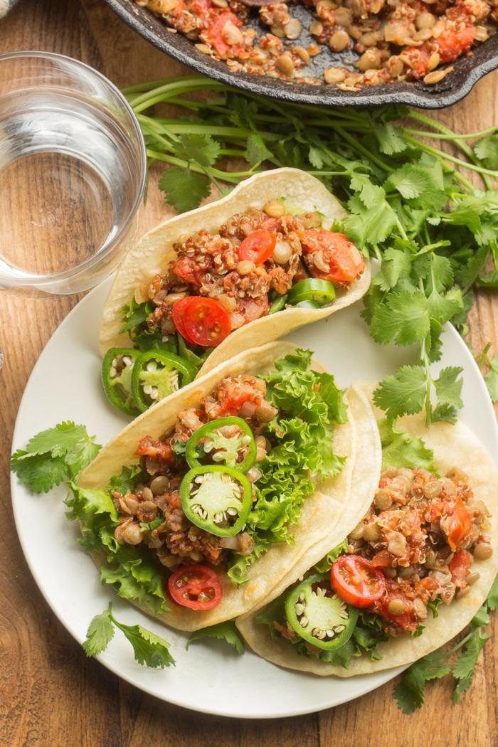 drei vegane Taccos auf einem weißen Teller, einfache schnelle Rezepte mit Quinoa und Linsen, grüne Paprika und anderes Gemüse