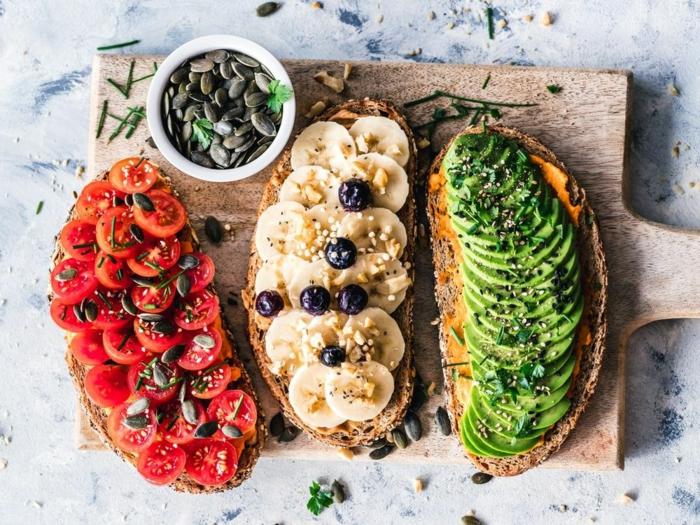 drei vegane toasts mit Avocado, Tomaten und Kürbiskerne, Erdnussbutter mit Bananen und Blaubeeren, auf einem hölzernen Brett, low carb rezepte vegan