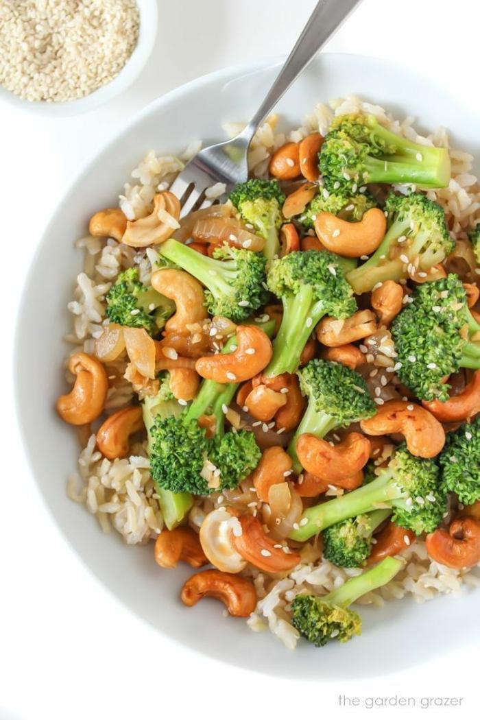 leckere Gemüse Rezepte vegan, Reis mit Brokkoli und gerösteten Cashewkernen in einer weißen Schale mit Gabel