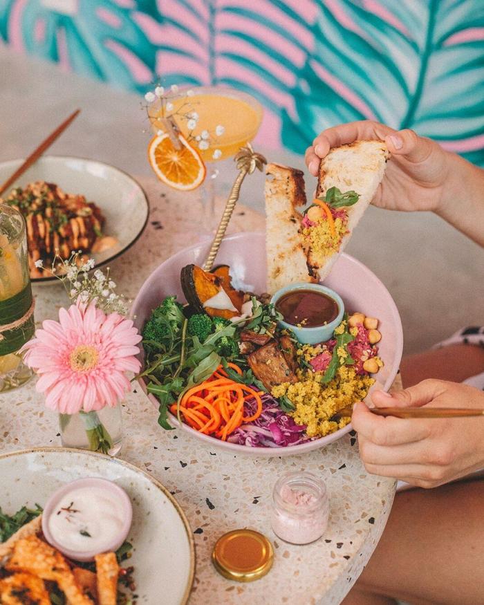 Veganer Brunch Rezepte, gesunder Buddhabowl mit gebratenen Auberginen und Gemüse, schöne pinke Blume in einer Vase,